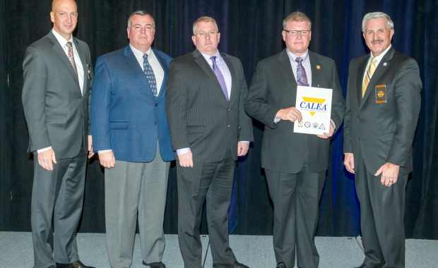 Danvers Police Captain/Accreditation Manager Patrick Ambrose (left), Lieutenant James Lovell (middle), and Chief Neil Ouellette (second from right) receive the CALEA Re-Accreditation Award from CALEA officials. Pictured are Executive Director W. Craig Hartley Jr. (Second from left) and Commission Chairman J. Grayson Robinson (right). (Courtesy of the Danvers Police Department)