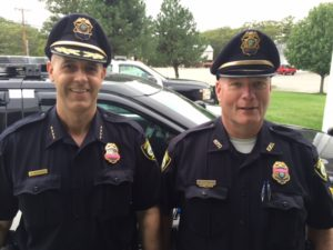 Left-to-right: Officer NAME and Officer NAME donning pink bands on their badges in support of MASS C.O.P.'s Breast Cancer Awareness Campaign.