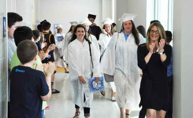 Rockland High School Seniors Macie Jones (middle-left holding blue folder) and Emily McLaughlin walk the halls of the Rogers Middle School 5th grade hallway as Assistant Principal Cheryl Schipper applauds. (Courtesy Photo)