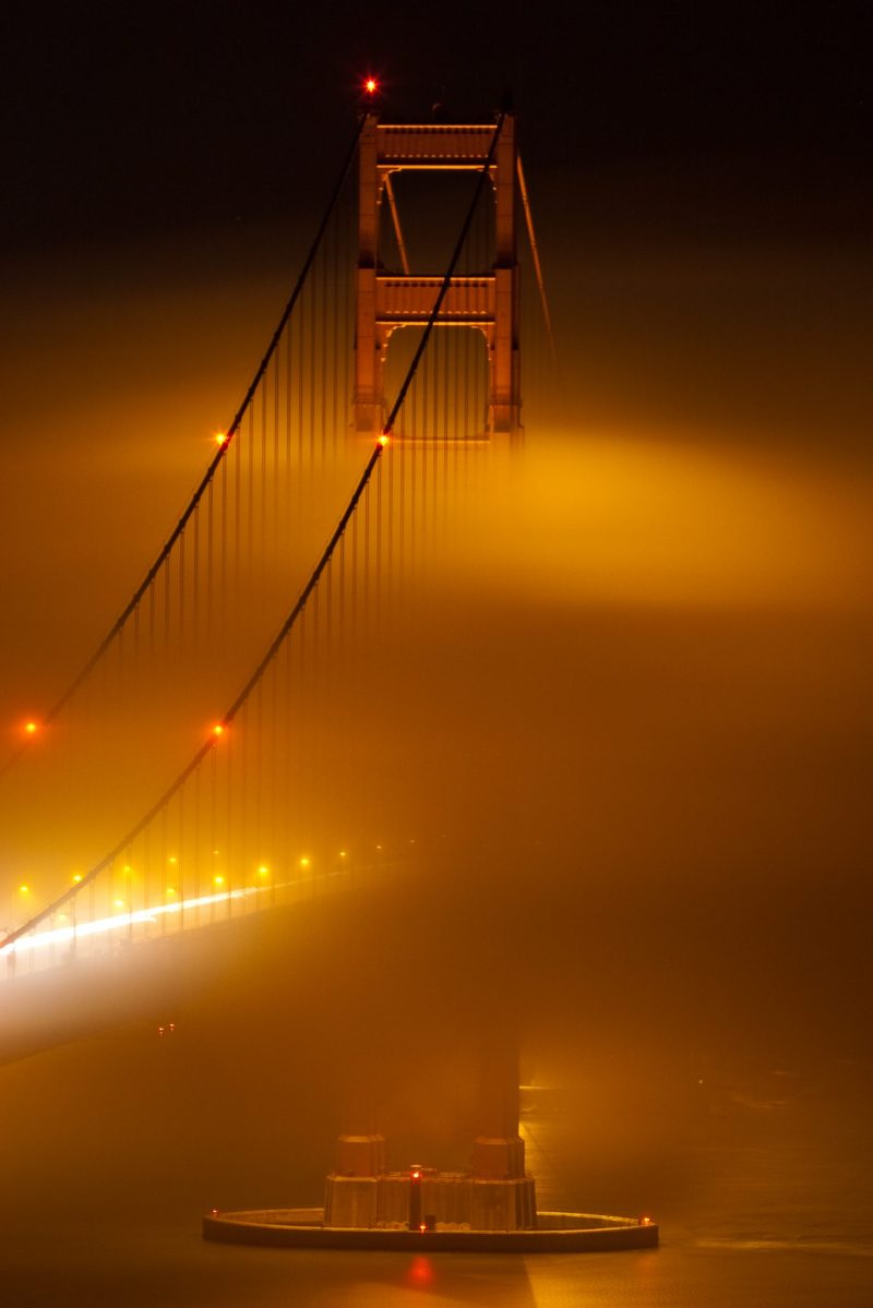 South Tower of the Golden Gate Bridge with nighttime fog swirling around it