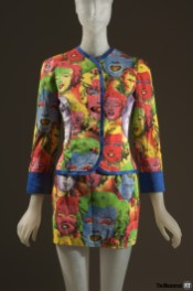 Suit consisting of cotton/silk blend cropped jacket and mini skirt with multi-color allover Andy Warhol print featuring faces of Marylin Monroe and James Dean, blue trim with rows of topstitching and rhinestone buttons down CF jacket.