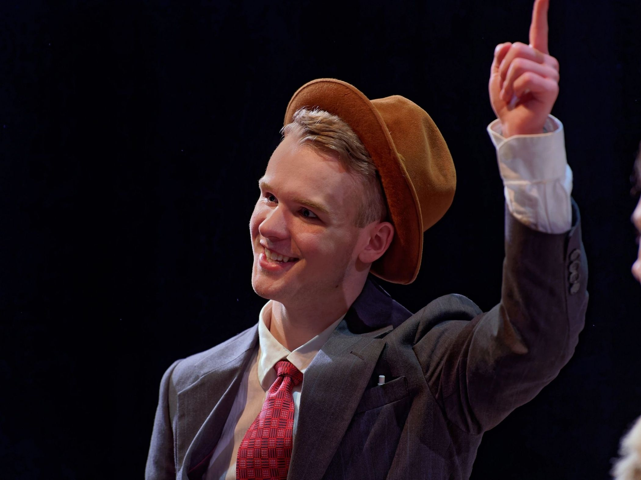 Theatre student in a suit and hat pointing up
