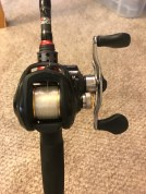 A bait-caster reel on its Abu Garcia fishing pole is full of line and awaits action.