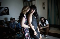 Two women drink and dance at a party.