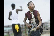 A child Liberian militia soldier loyal to the government walks away from firing on rebel forces across a key bridge while another taunts them, July 30, 2003. Chris Hondros/Getty Images