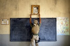 A U.S. Marine pulls down a picture of Iraqi leader Saddam Hussein at a school on April 16, 2003. Chris Hondros/Getty Images