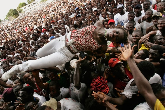 An unconscious woman is carried by supporters of Liberian presidential candidate George Weah after she fell ill from heat during a rally Oct. 8, 2005, in Monrovia, Liberia. This image is included in a new book of Chris Hondros' work, available through powerHouse Books this month. Chris Hondros/Getty Images
