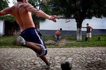 Boys play a game of soccer in the street using two trees as goal posts in Klosdorf, Romania, August 2010. Tim Dirven/Panos