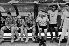 Men sit on a soccer bench during a game organized with teams mixed with players from the U.S. Army and Iraqi forces in Baghdad, June 2009. Christopher Anderson/Magnum