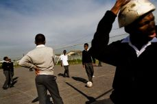 A boy wears a deflated soccer ball on his head while other boys play soccer at the iQhayiya Senor Secondary School in Cape Town, South Africa, on May 26, 2010. Dominic Nahr/Magnum