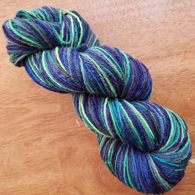 The sheep fleece to sock yarn skein dyed green, purple and blue