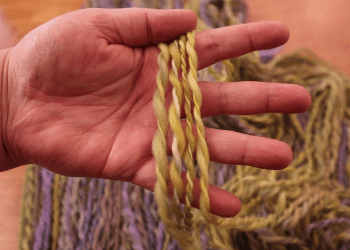 A hand holds up several strands of green and yellow handspun yarn.