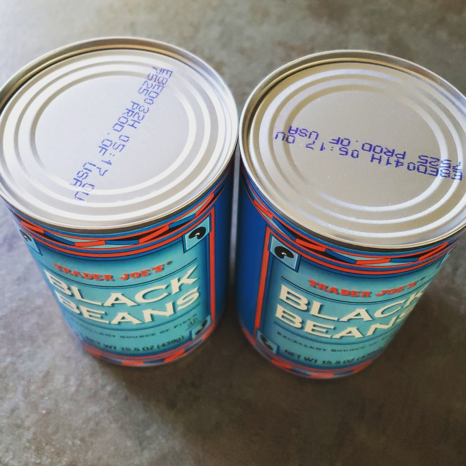 Two unopened can of Trader Joe's brand black beans
