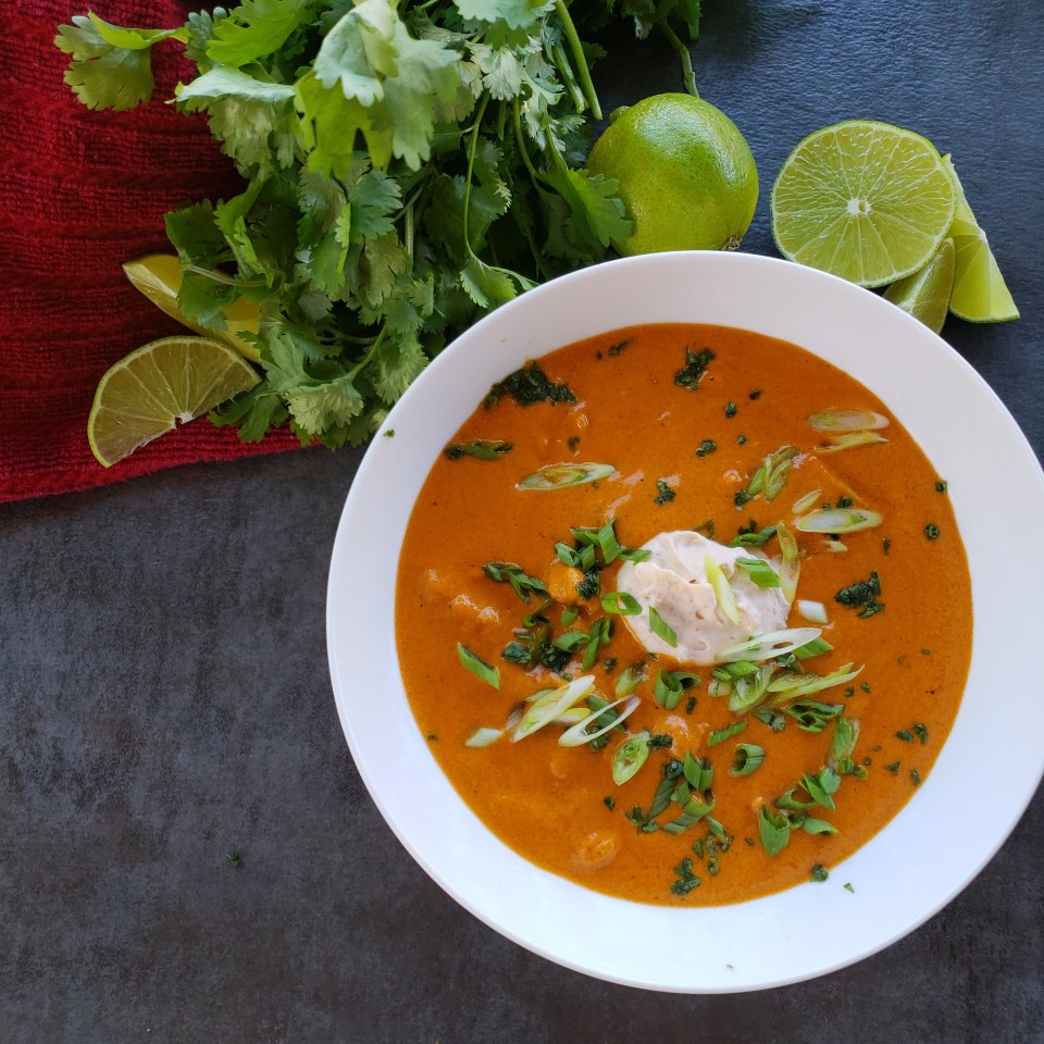 A bowl of soup with green and white garnish with cilantro and limes on side