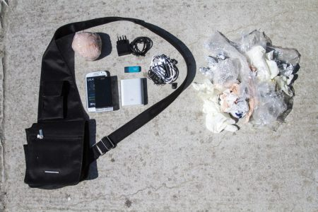 "The contents of a 34-year-old refugee's bag: Anonymous, 34, from Syria ""I had to leave behind my parents and sister in Turkey. I thought, if I die on this boat, at least I will die with the photos of my family near me."" Money (wrapped to protect it from water), Old phone (wet and unusable) and new smart phone, Phone chargers and headphones (plus extra battery charger), 16GB flash drive (containing family photos)."