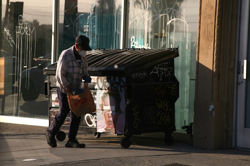 A man finishes searching through the dumpster bin for cans in Silver Lake, Los Angeles