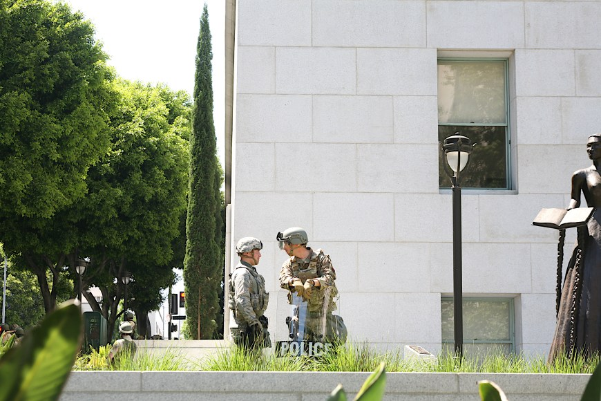 A police officer and National Guard service-member exchange a word at the Hall of Justice in downtown Los Angeles