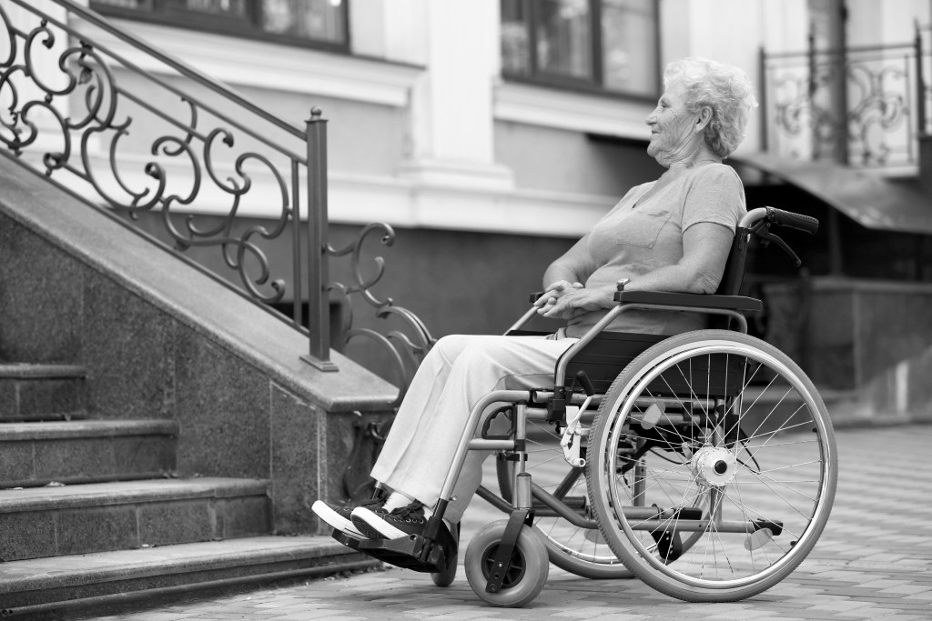 A wheelchair user at bottom of steps