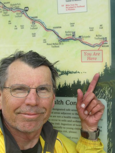 Jim-Schmid-pointing-to-end-of-Trail-on-Mullan-kiosk-Trail-of-the-Coeur-d'Alenes-ID-5-15-2016
