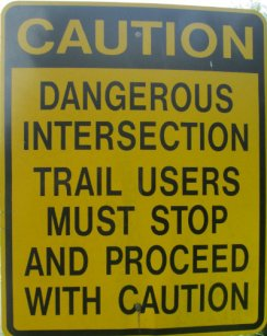 Caution_dangerous_intersection_trail_users_must_stop_and_proceed_with_caution_sign_Chief-Ladiga-Trail-AL-2015-06-01