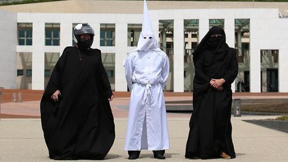 ชายสามคนในชุดมีผ้าและหมวกกันน็อคคลุมศีรษะที่หน้ารัฐสภากลาง
