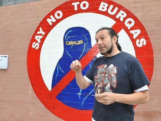 """นาย Sergio Redegalli กับภาพฝาผนัง """"Say no to the burqas"""" ที่ย่าน New Tow"""