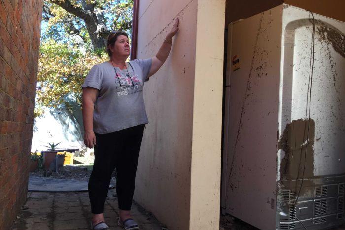 นาง Sindy Duffield กำลังชี้ให้เห็นระดับน้ำท่วมที่บ้านของเธอในย่าน Picton เธอเป็นอีกคนหนึ่งที่กรมธรรม์ประกันไม่ครอบคลุมบ้านของเธอ …อ้อน้ำท่วมในออสเตรเลียส่วนใหญ่ท่วมแล้วแห้งเร็ว ไม่เหมือนบ้านจิงโจ้นิวส์ที่เมืองไทยเมื่อครั้งน้ำท่วมใหญ่ท่วมระดับเดียวกับบ้านนาง Duffield น้ำขังอยู่อย่างนั้นสามเดือนครับ : ภาพจากสำนักข่าว ABC