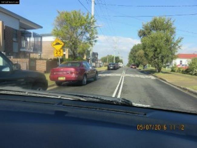 รถมาสด้าสีแดงของนายสุรศักดิ์ ดวงรัตน์จะสังเกตเห็นลูกล้อด้านซ้ายเข้าไปอยู่ในกรอบขอบเส้นขอบทาง ตอนที่ตำรวจทางหลวงผ่านมาเจอรถคันอื่นที่จอดอยู่ได้หายไปหมดแล้ว เหลือแต่รถโตโยต้าสีแดงและรถสีดำขวามือที่ถูกปรับ : ภาพจาก NSW Office of State Revenue