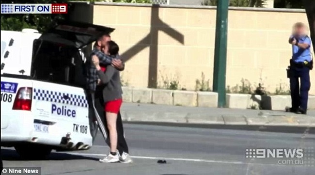 นาย Brendan Lindsay จับตัวนาง Sheila Tran เป็นตัวประกันที่ภายนอกร้าน Lunch Club Deli โดยมีตำรวจเตรียมพร้อมลั่นกระสุนปืน : ภาพจากทีวี 9 News