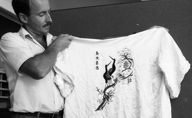 จ่าตำรวจนักสืบกำลังถือชุดเสื้อคลุมผ้าไหมสีขาว (กิโมโน) ที่คนร้ายทำตกไว้ในที่เกิดเหตุ : ภาพจากนสพ. The West Australian
