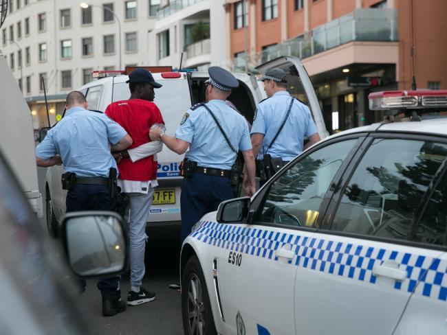 ตำรวจขณะจับหนึ่งในสมาชิกแก๊งวัยขึ้นรถตำรวจ : ภาพชั่วคราวจากนสพ. The Telegraph