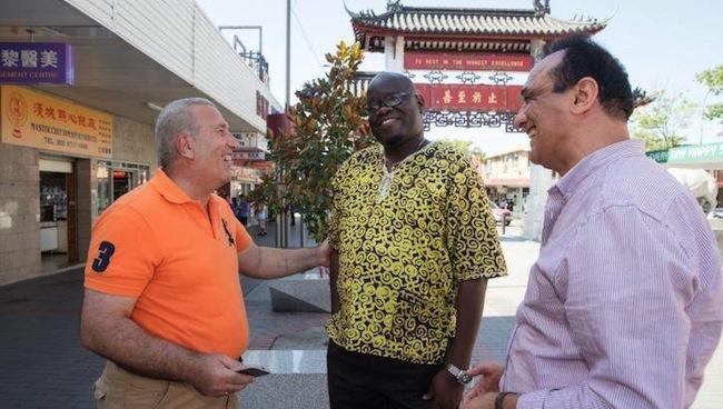 นาย Tony Fare ผู้ลี้ภัยชาวซีเรีย (คนเสื้อเหลือง) กับนาย Clement Meru ผู้จัดการพหุวัฒนธรรมชุมชนของ CORE Community Services และนาย Murshid Amar เจ้าหน้าที่ของ CORE ขณะอยู่ที่ย่าน Cabramatta ของเขตฯ Fairfield : ภาพจากนสพ. The SMH