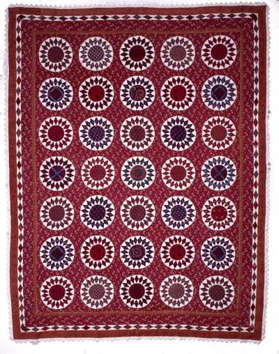 Beautiful quilt made of predominately red fabrics, featuring 35 pieced Sunflower blocks