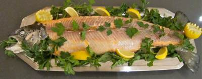 a whole Poached Salmon on a long narrow metal platter with head and tail, skin removed, garnished with lemon wedges and parsley