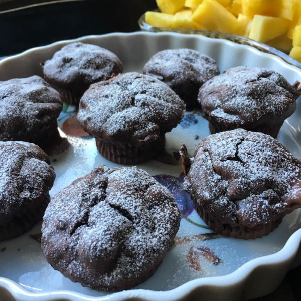 Jittery Flourless Chocolate Muffins, out of the silicone cups, in a ceramic pie plate with cut up pineapple on the side