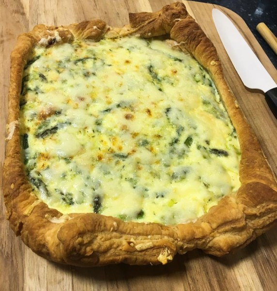 whole asparagus gruyere tart on a wooden cutting board ready to be sliced