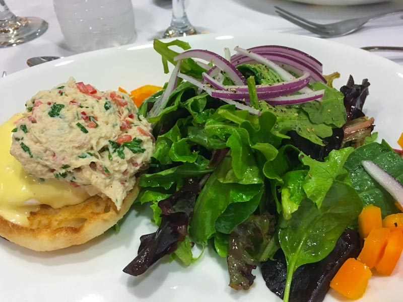 field green salad, poached egg on English muffin toast, topped by bechamel sauce and crab salad