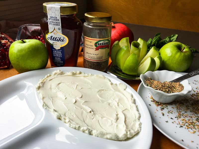 Honey Yogurt Dip in a divided white plate with sliced Granny Smith apple, whole Granny Smith apples, pomegranate seeds, whole pomegranate, Greek Attiki honey in the jar and Yogurt Seasoning