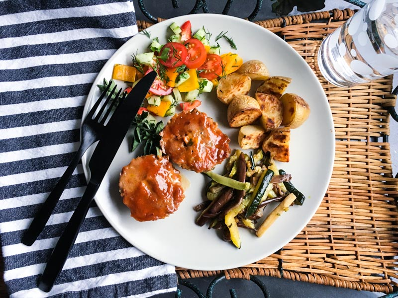 Lamb Meatloaf with Sweet and Spicy Topping cooked in muffin cups. Served on a white plate with grilled zucchini and eggplant, roasted sweet potatoes and salad. Overhead shot, with a striped napkin. on a woven tray, with black stainless steel cutlery.
