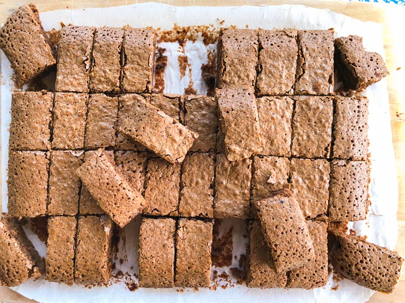 Cooked Espresso Brownies on a wooden board, sliced into 40 portions with some pieces lifted up. Over head shot.