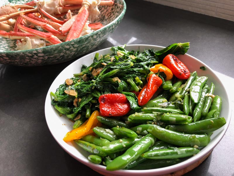White bowl with snap peas, snow pea leaf shoots, roasted peppers. In the background there's a green and white bowl with cooked Snow Crab legs.