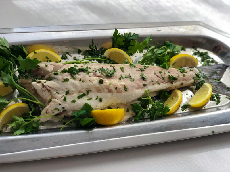 Cooked Mediterranean bass on tray, skin and head removed, garnished with lemon and parsley