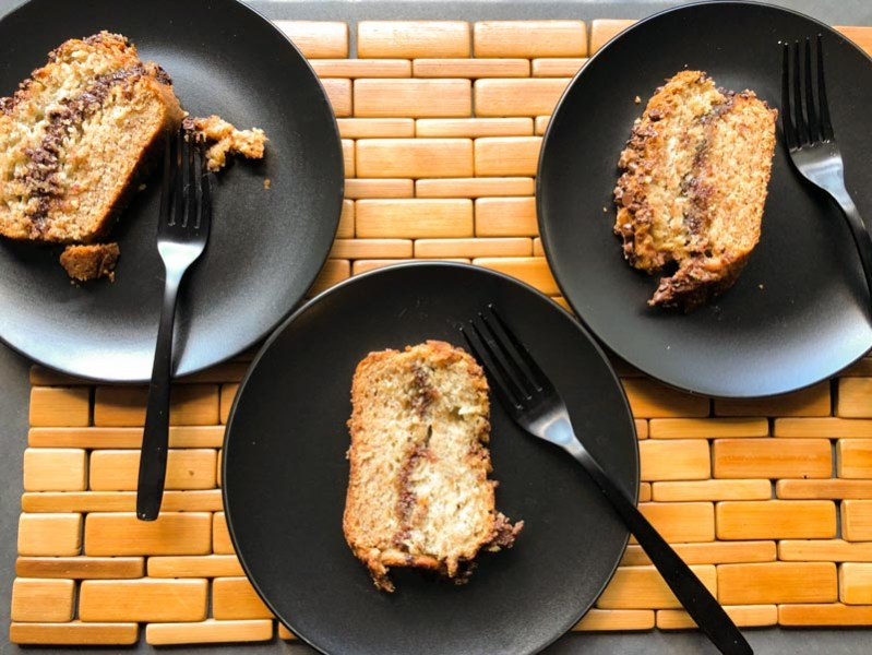 Simply the Best Banana Cake fresh out of the oven, sliced and placed on black plates with black forks.
