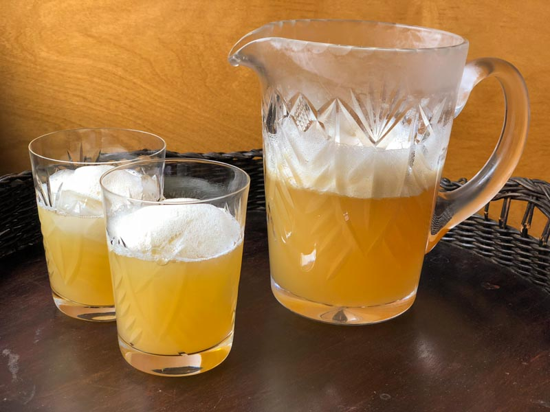 Honey Lemon Ginger Tea in a cut glass pitcher and two cut glass tumblers with froth on top.