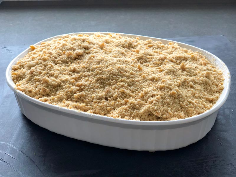 apple crisp before baking in a white pyrex dish