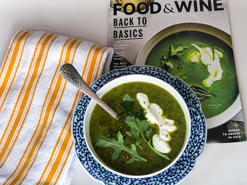 Bowl of Rocket Soup on a white tray with magazine and tea towle