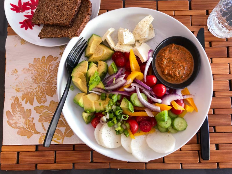 Roasted Red Pepper Pesto served in a small dressing dish inside a single serve salad bowl with an assortment of raw vegetables and healthy brown bread on the side.. Photographed from above.