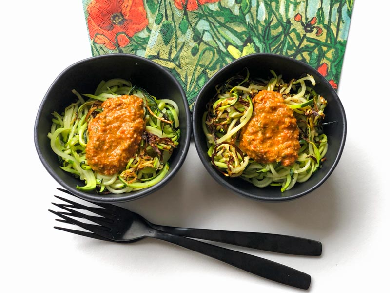 Roasted Red Pepper Pesto served on roasted zoodles in small black bowls with small black forks and colourful napkins on a white background.