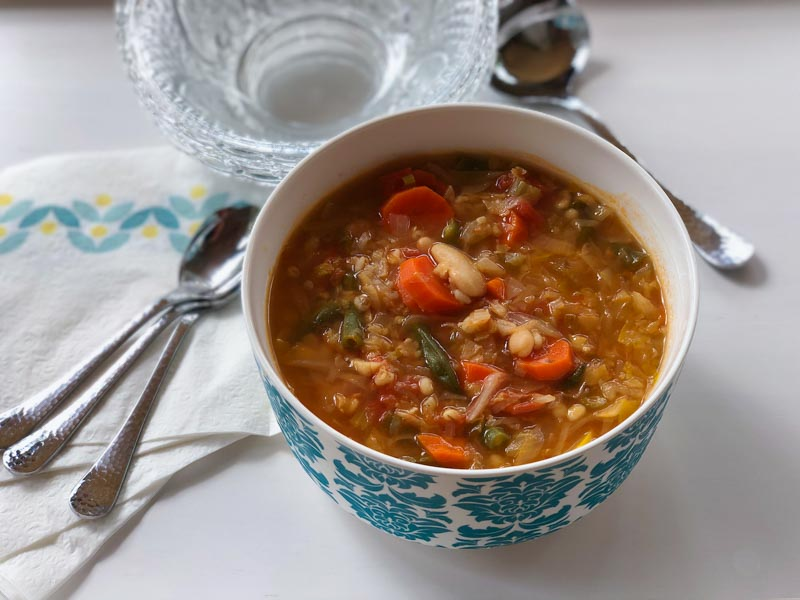 Minestrone Meets Bubbie's Cabbage Soup in a serving bowl with napkins, spoons and a serving spoon
