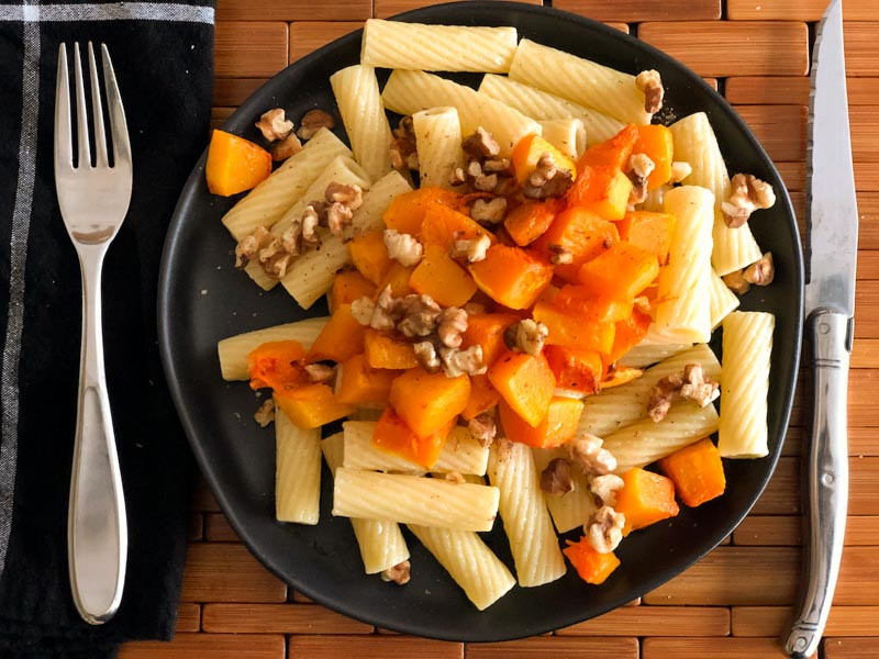 Roasted Butternut Squash Pasta served on black plate with napkin and cutlery.